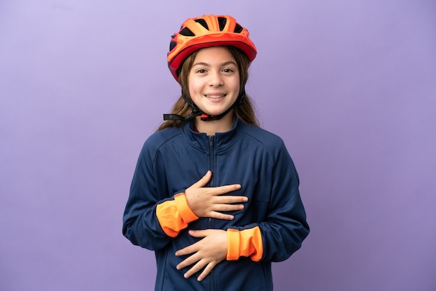 Маленькая кавказская девушка изолирована на фиолетовом фоне, много улыбаясь