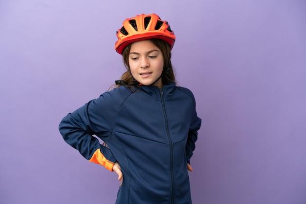 努力したために腰痛に苦しんで紫色の背景に孤立した小さな白人の女の子 Premium写真