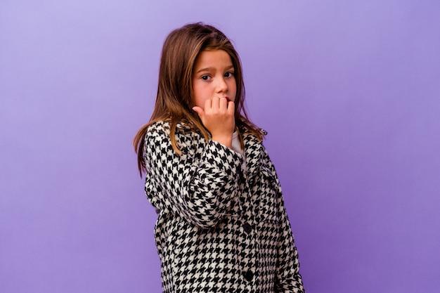 Маленькая кавказская девочка изолирована на фиолетовых кусающих ногтях, нервничает и очень тревожится.