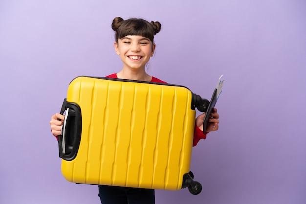 Маленькая кавказская девушка изолирована на фиолетовой стене в отпуске с чемоданом и паспортом