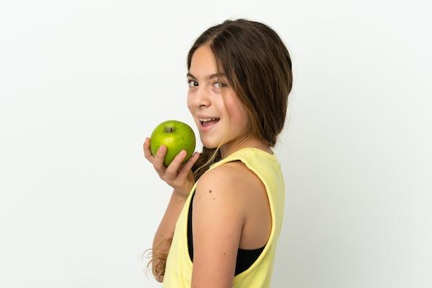 Маленькая кавказская девочка, изолированные на белом фоне, ест яблоко