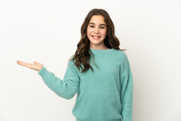 Маленькая кавказская девушка изолирована на белом фоне, держа воображаемое пространство на ладони, чтобы вставить объявление