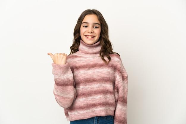 Маленькая кавказская девушка, изолированные на белом фоне, указывая в сторону, чтобы представить продукт