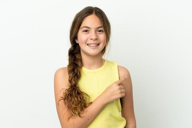 제품을 제시하기 위해 측면을 가리키는 흰색 배경에 고립 된 어린 백인 소녀
