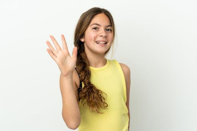 Маленькая кавказская девушка изолирована на белом фоне, салютуя рукой с счастливым выражением лица