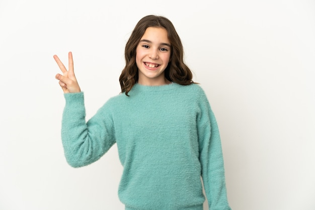 Маленькая кавказская девочка, изолированные на белом фоне, улыбается и показывает знак победы