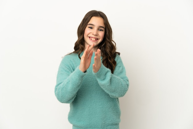 Маленькая кавказская девушка изолирована на белой стене аплодирует после презентации на конференции