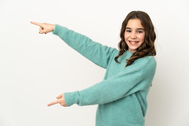 측면에 손가락을 가리키고 제품을 제시하는 흰 벽에 고립 된 어린 백인 소녀