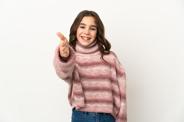 좋은 거래를 닫기 위해 악수하는 흰 벽에 고립 된 어린 백인 소녀