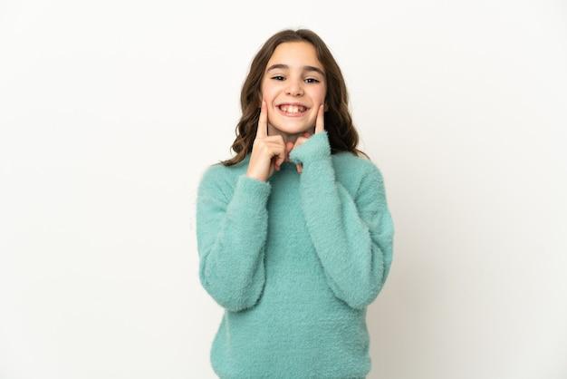 행복하고 즐거운 표정으로 웃고 흰 벽에 고립 된 어린 백인 소녀