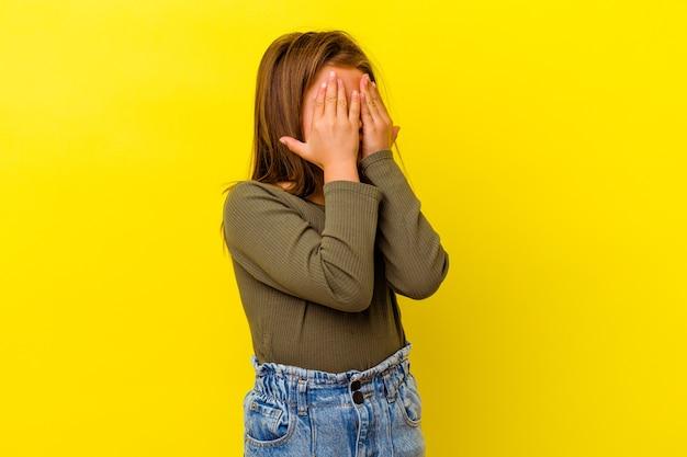 Маленькая кавказская девушка изолирована на желтых испуганных закрывающих глазах руками.