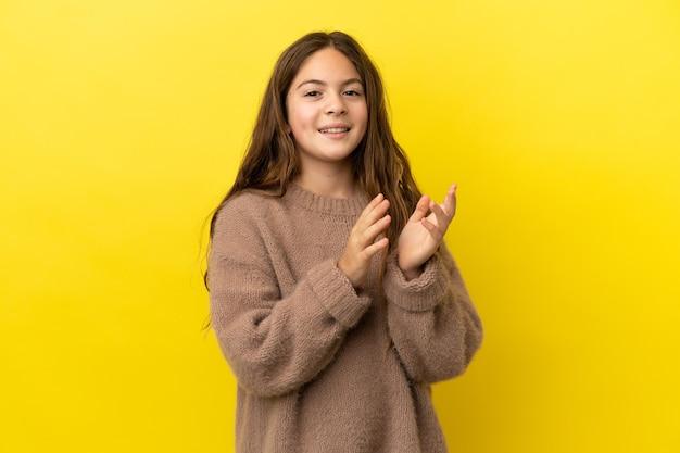 회의에서 발표 후 박수 갈채 노란색 배경에 고립 된 어린 백인 소녀