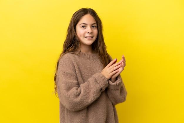 노란색 배경 박수에 고립 된 어린 백인 소녀