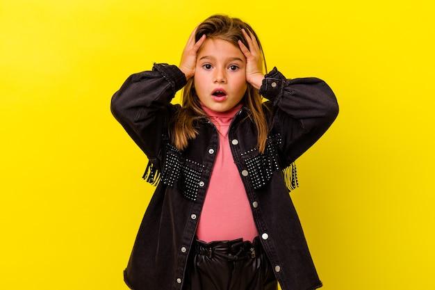 ショックを受けている黄色の背景に孤立した小さな白人の女の子、彼女は重要な会議を覚えています。