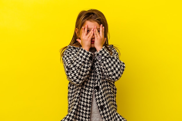 Маленькая кавказская девочка, изолированная на желтом фоне, моргает сквозь пальцы, испугавшись и нервнича.