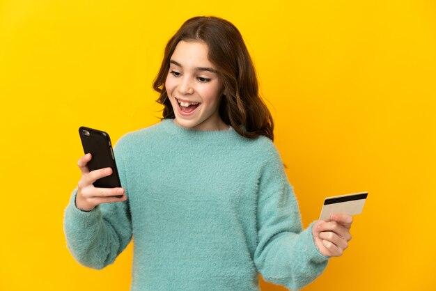 Маленькая кавказская девушка изолирована на желтом фоне, покупая с мобильного с помощью кредитной карты