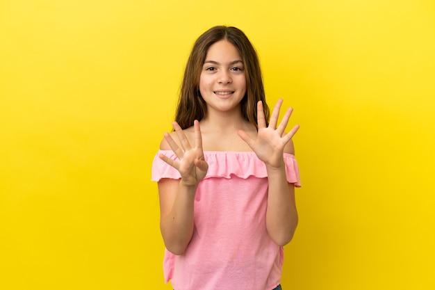 Маленькая кавказская девушка изолирована на желтом фоне, считая девять пальцами