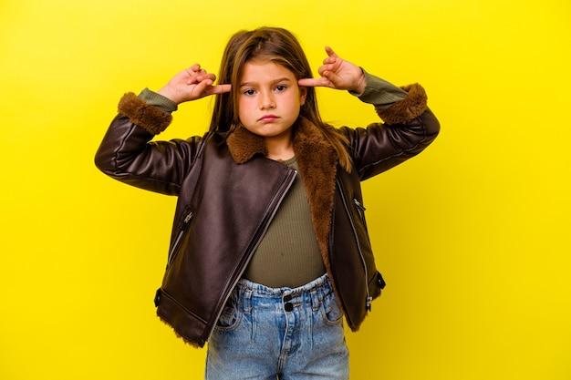 Маленькая кавказская девочка, изолированная на желтом фоне, сосредоточилась на задаче, держа указательные пальцы, указывая головой.