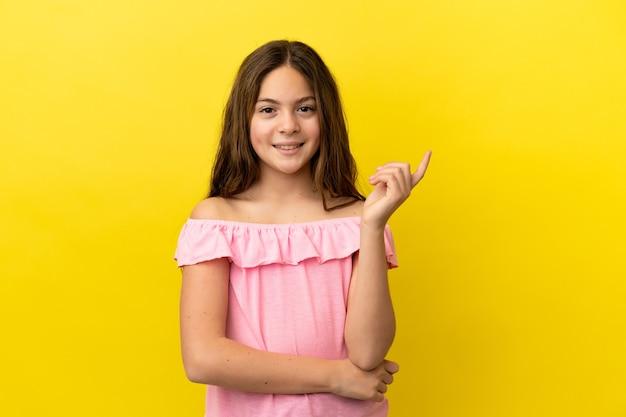 노란색 배경에 고립되어 행복하고 위를 가리키는 백인 소녀
