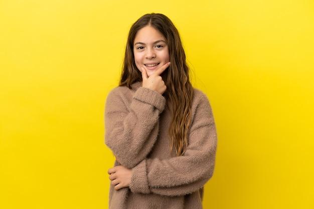 Маленькая кавказская девочка, изолированных на желтом фоне, счастлива и улыбается