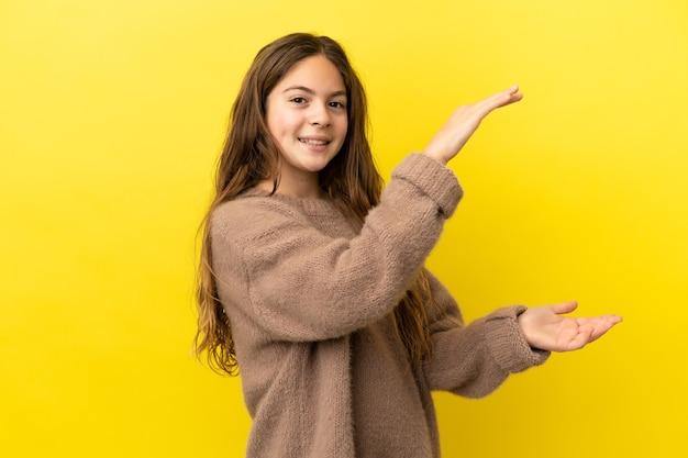 광고를 삽입하기 위해 copyspace를 들고 노란색 배경에 고립 된 어린 백인 소녀