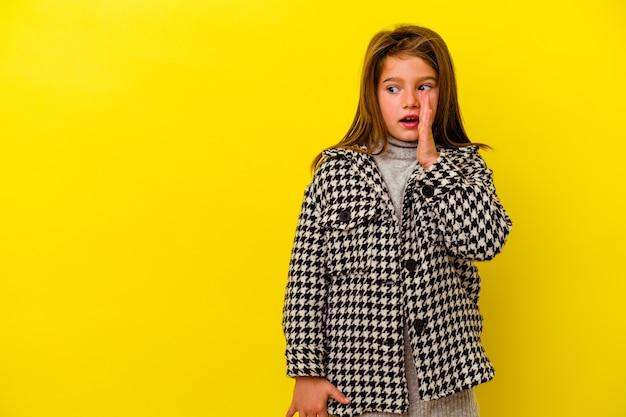 노란색 배경에 고립 된 어린 백인 소녀는 비밀 뜨거운 제동 뉴스를 말하고 옆으로 찾고