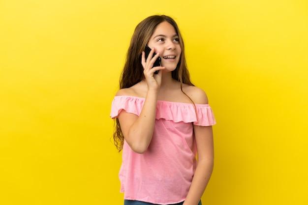 携帯電話との会話を維持している黄色の背景に分離された白人の少女
