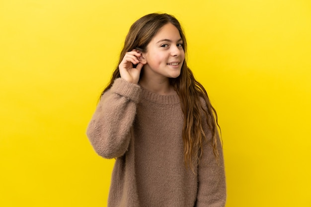 耳に手を置くことによって何かを聞いて黄色の背景に分離された白人の少女