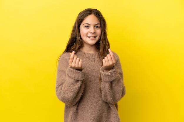 Маленькая кавказская девушка изолирована на желтом фоне, делая денежный жест