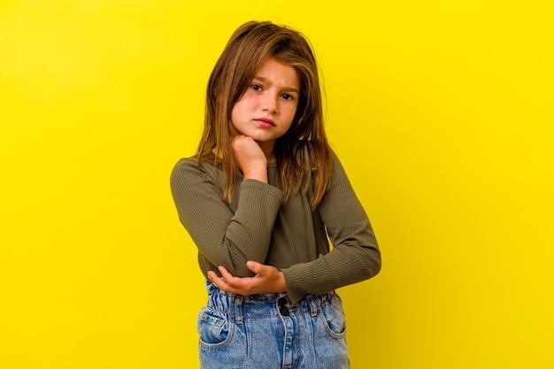 ひじをマッサージし、悪い動きの後に苦しんでいる黄色の背景に孤立した白人の少女。