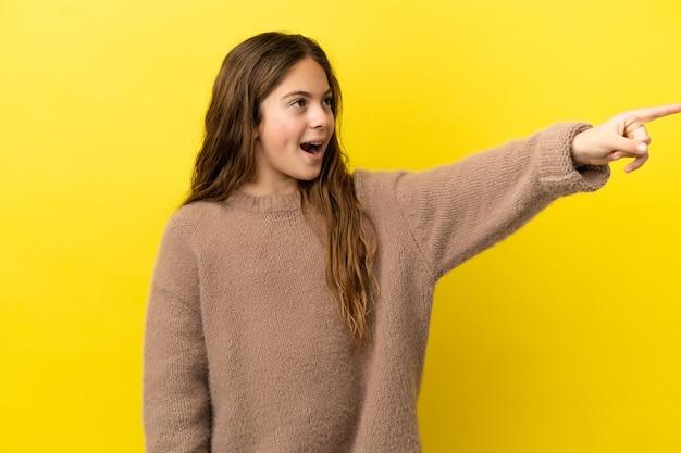 離れて指している黄色の背景に分離された白人の少女