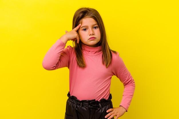 黄色の背景に孤立した小さな白人の女の子は、指で寺院を指して、考えて、タスクに焦点を当てました。