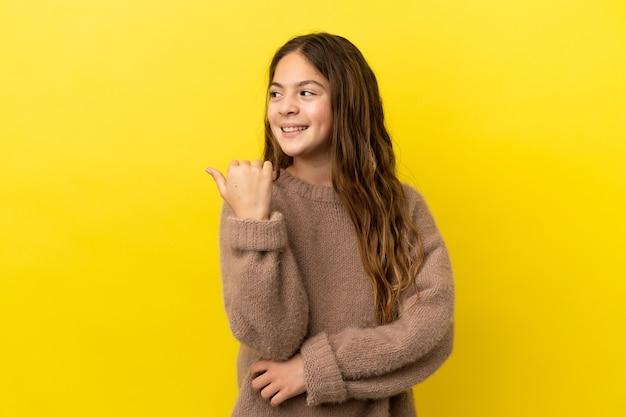 Маленькая кавказская девушка изолирована на желтом фоне, указывая в сторону, чтобы представить продукт