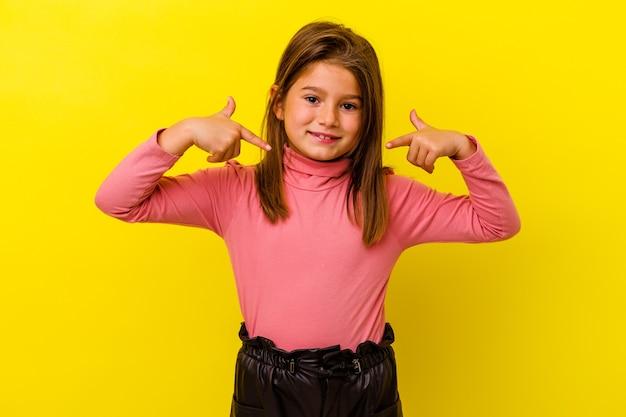 黄色の背景に孤立した小さな白人の女の子は、指で下向き、前向きな気持ちです。