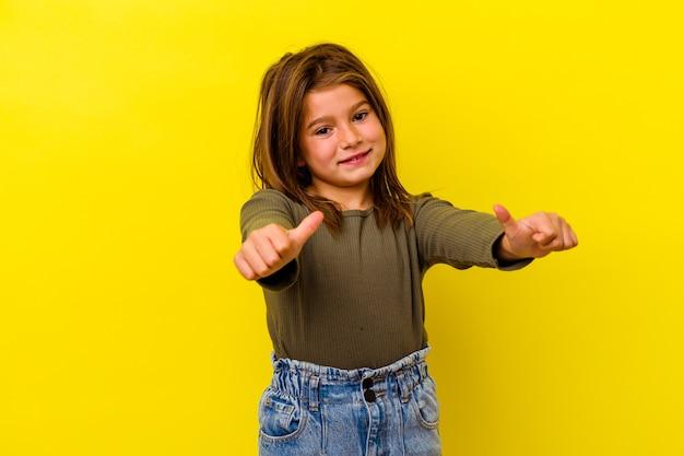 黄色の背景に孤立した小さな白人の女の子は、両方の親指を上げて、笑顔で自信を持っています。