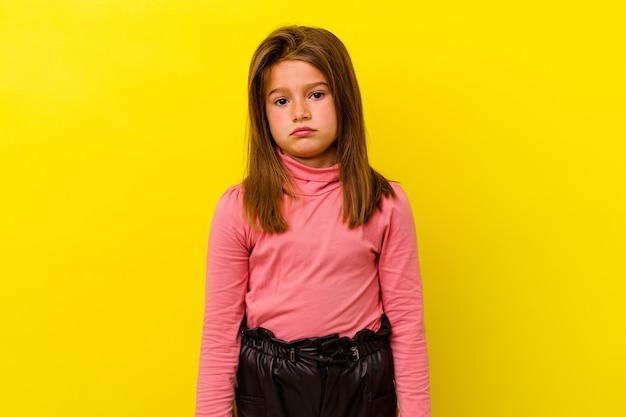 Маленькая кавказская девочка, изолированных на желтом фоне, грустное, серьезное лицо, чувствуя себя несчастным и недовольным.