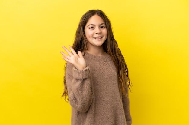 Маленькая кавказская девушка изолирована на желтом фоне, салютуя рукой с счастливым выражением лица