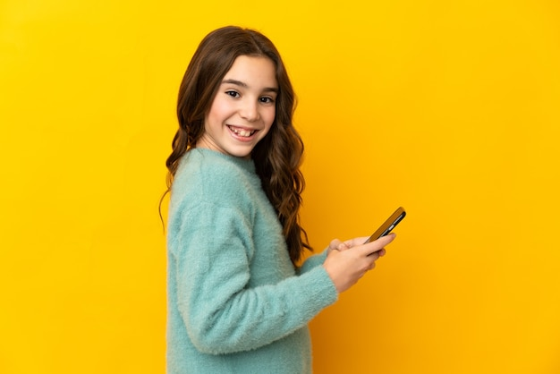 Маленькая кавказская девушка изолирована на желтом фоне, отправляя сообщение или электронное письмо с мобильного телефона