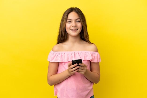 노란색 배경에 격리된 백인 소녀가 휴대전화로 메시지를 보냅니다.
