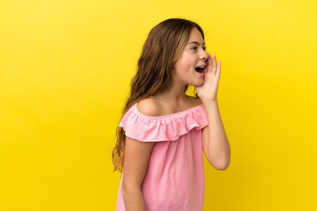 Маленькая кавказская девочка, изолированная на желтом фоне, кричит с широко открытым ртом в сторону