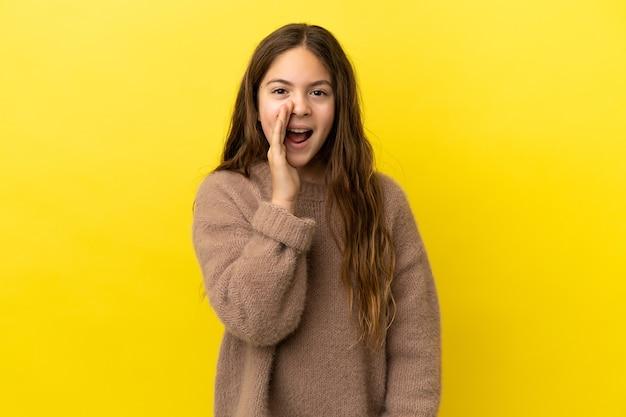 Маленькая кавказская девочка, изолированная на желтом фоне, кричит с широко открытым ртом