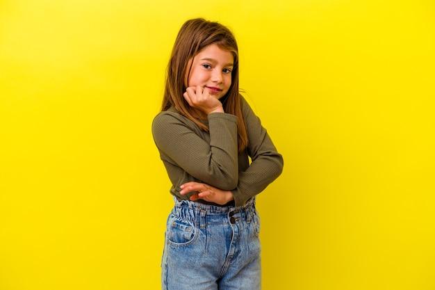 黄色の背景に孤立した小さな白人の女の子は、手であごに触れて、幸せで自信を持って笑っています。