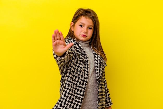 노란색 배경 서 뻗은 손으로 정지 신호를 표시, 방지에 고립 된 어린 백인 소녀.