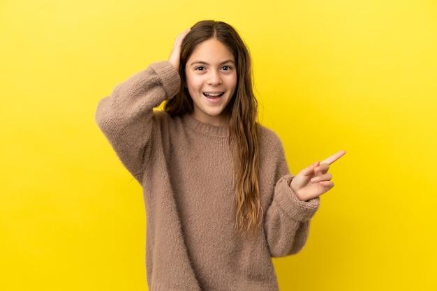 黄色の背景に孤立した小さな白人の女の子は驚いて、人差し指を横に向けます