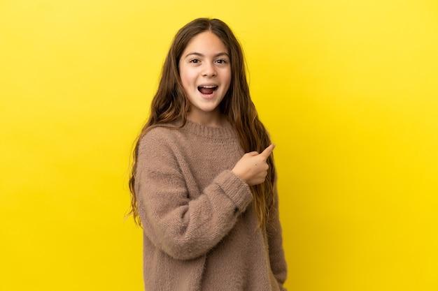 Маленькая кавказская девушка изолирована на желтом фоне удивлена и указывает сторону