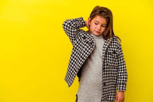 Маленькая кавказская девушка изолирована на желтом фоне, касаясь затылка, думая и делая выбор.