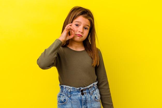 비밀을 유지하는 입술에 손가락으로 노란색 배경에 고립 된 어린 백인 소녀.