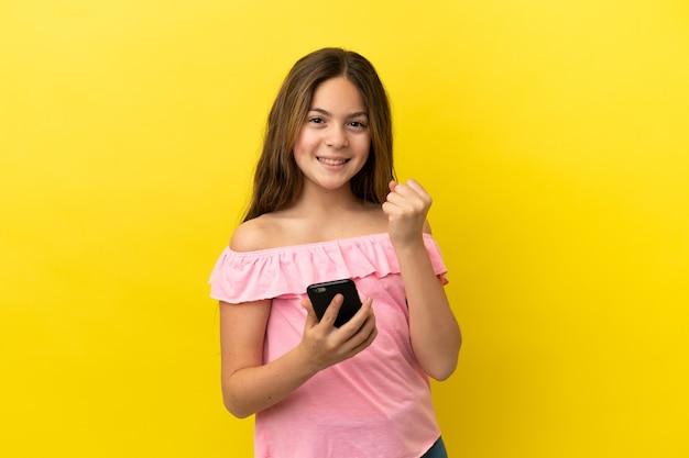 Маленькая кавказская девушка изолирована на желтом фоне с телефоном в позиции победы