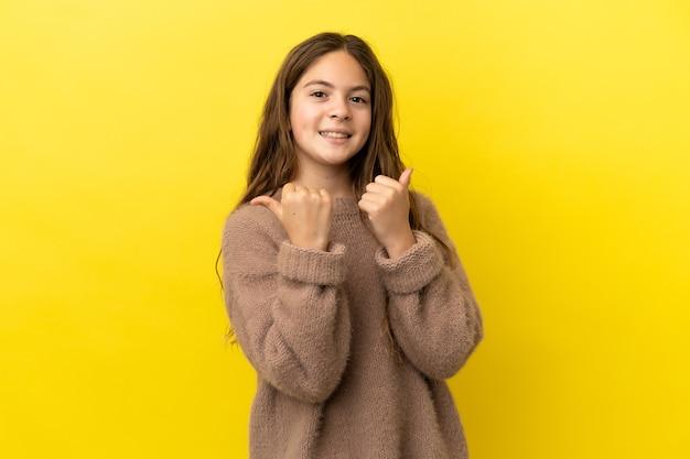 엄지손가락 제스처와 웃는 노란색 배경에 고립 된 어린 백인 소녀