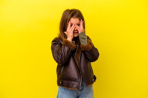 Маленькая кавказская девочка, изолированная на желтом, моргает в камеру сквозь пальцы, смущенно закрывая лицо.